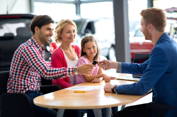 car dealer selling new car to young family